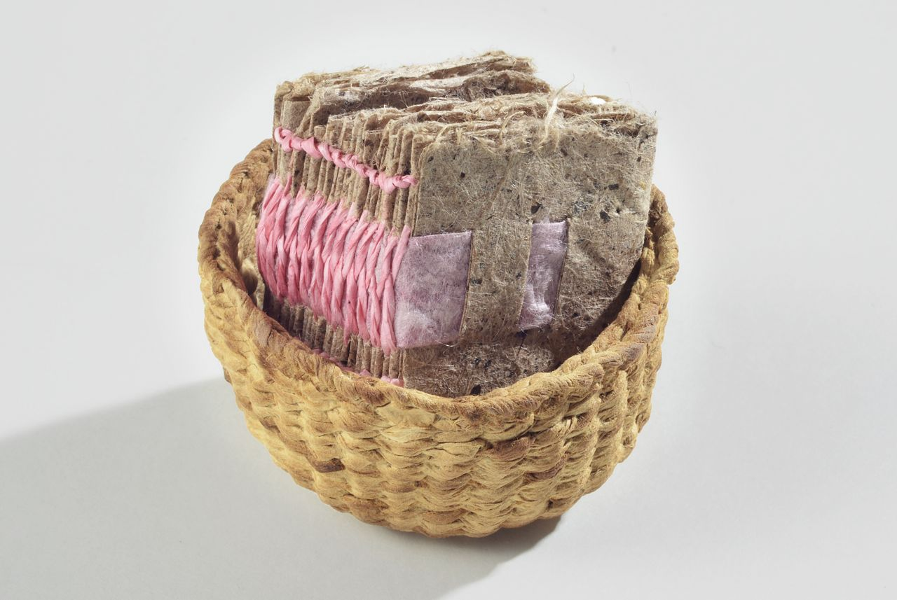 "Book in a basket (2011). Pen on handmade slippery elm and dak paper, cochineal-dyed hanji and pine paper yarn. Book: 1.375 x 1.25 x 1"". Oberlin College Art Library Collection."