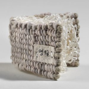 """Myeongwol / Bright Moon Talisman (2010). Hanji, Pine Paper Yarn, Pen And Inkjet Print On Handmade Paper. Edition Of Four. 2 X 2.25 X 1.25"""". Various Collections."""