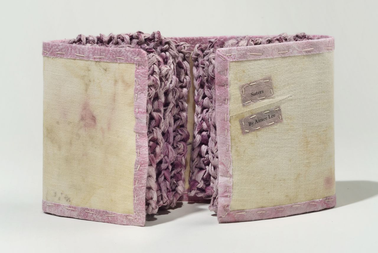 "Sisters (2011). Inkjet print on dyed hanji, dyed and knitted handmade mulberry paper, eco-printed linen, thread. 5 x 8 x 1.5"" closed, 17"" wide open. Oberlin College Art Library Collection."